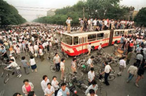 Beijing residents using a bus as a roadblock to stop troops from advancing to Tiananmen Square in June 1989
