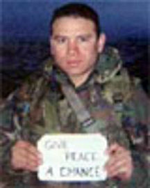 Ex-Sgt. Camilo Mejia holding an anti-war sign in Iraq. After refusing to report for duty, he was sentenced to a year in jail.