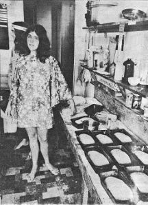 Photo of tired-looking young woman in kitchen surrounded by many loaves of baked bread.