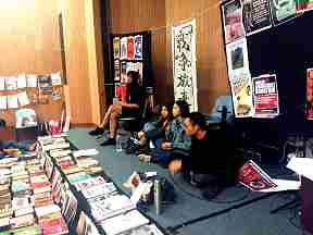 "Collective members from a vegan restaurant in a working class community with a ""pay what you feel is ight"" free/autonomoous pricing operation presenting at the Hong Kong book fair. Image shows 4 people sitting on a low stage, many publications and posters in Chinese and English are visible."