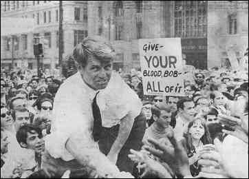 Robert F. Kennedy, May 15, 1968. Sign held by protester reads: Give YOUR blood, Bob. All of it!