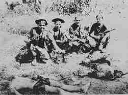 Photo shows four Marines sitting in a field. In front of them are various body parts, including heads. They are all heavily armed.