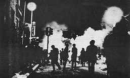 Photo of nighttime street scene with smoke and/or fire in the background.