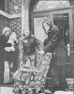 Photo shows two female officers removing furniture while evicted woman beams with approval.