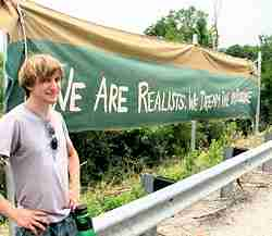 "Photo of a smiling young man standing near a large banner that reads ""We are the realists: We demand the impossible."""
