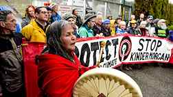 Photo shows a protest rally against the planned Kinder Morgan pipeline in British Columbia, Canada. In the foreground an indigenous woman is seen singing and beating a ceremonial drum.