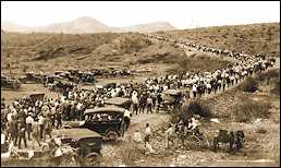 Photo shows hundreds of people, with cars and belongings, stranded in a desert setting.