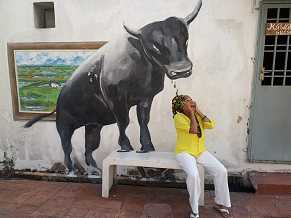 Photo shows a brown-skinned woman sitting on a bench. On a wall behind her is a life-size painting of a bull, appearing as if its forehooves are on the bench. Mbeke pretends to be afraid.