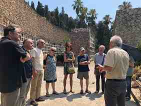 Photo showing a small group of people standing in a circle in an outdoor setting, surrounded by stone walls, in full sun.