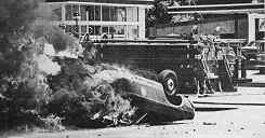 Photo showing 2 overturned cars with smoke rising from one of them.