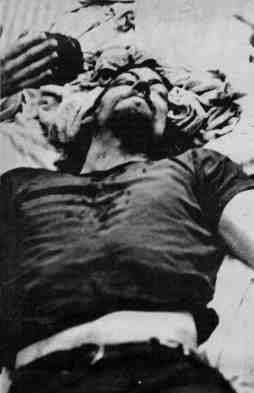 Photo showing a young man prostrate on the ground being given medical attention. Dark spots, possibly blood appear on his shirt. There is no identifying information with the photo in the print original.