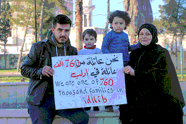 "Photo shows a man, a woman and two small children holding a sign reading ""We are one of 760,000 families in Idlib."""