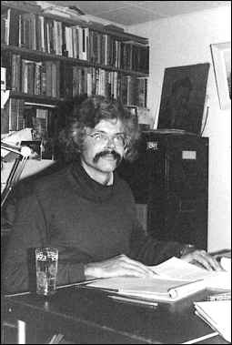 Photo shows David Porter in the midst of reading at his desk.