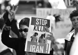 "Photo shows a person giving a V-sign and holding a sign that reads, ""Stop killing in Iran."""