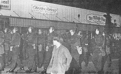 photo, nighttime street scene shows large group of police in riot garb looking manacingly at groups of young people.