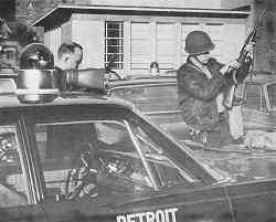 photo shows two riot-suited officers examining and/or loading rifles