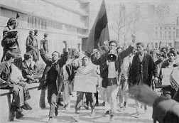 Photo shows a political demonstration with flags, signs and a man speaking through a bullhorn.