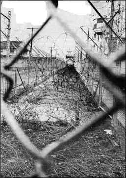 Photo shows double barbed-wire fence and watchtower at Fort Dix stockade.