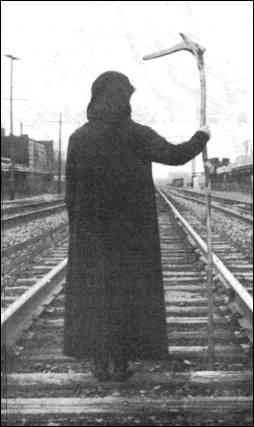 Grim Reaper. Photo shows the back of a human figure in dark attire holding a scythe and standing on a railroad track.