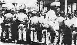 Photo shows a line of helmeted officers facing a crowd of protesters.