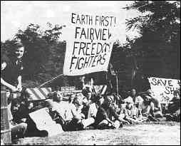 "Photo shows protesters sitting on ground, blocking road. One sign reads, ""Earth First! Fairview Freedom Fighters."""