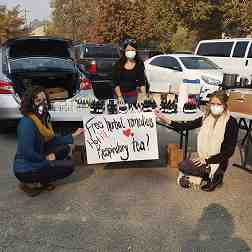 Three women wearing protective face masks share herbal remedies from a table in a parking lot.