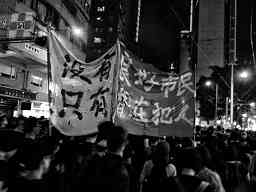 Photo, night demo in Hong Kong showing anarchist banner with Chinese characters