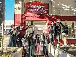 A color painting shows a group of about 15 people in front of the Berkeley Free Clinic, most saluting with raised fists.