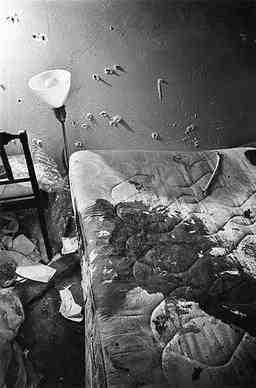 Photo shows the bed in which Fred Hampton was shot by Chicago police. Image includes many bullet holes in wall and much blood on matress.