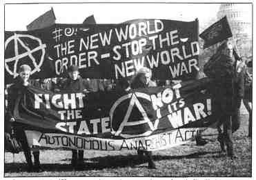 """Photo shows several people holding banners and flags. One banner reads, """"Fight the state, not its war!."""""""