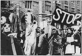 "Photo shows a group of women with large puppets and a banner reading ""Stop War."""