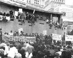 """Photo shows a crowd of protesters with signs reading """"Bring the troops home now."""" A banner reads """"Women's liberation movement, U.S. & Vietnam solidarity."""