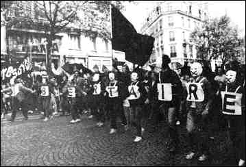 Photo shows a group of supporters in the street, some wearing letters spelling out LIBERTAIRE.
