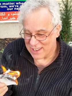 Photo shows an older Bill Greenshields with a flaming paper object