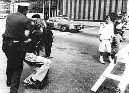 Photo shows an officer exerting force on the arm and neck of a protester as children look on.