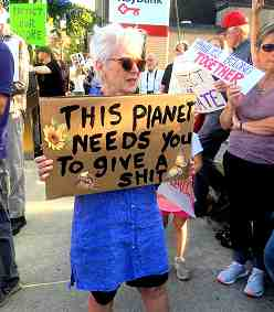 "Photo shows an elderly woman holding a sign reading ""This planet needs you to give a shit."""