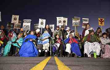 Photo shows a crowd of colorfully-dressed native Hawiians blocking a highway at night.