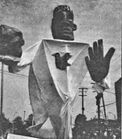 Photo shows a 15-foot tall puppet at a protest demonstration.