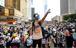 Photo shows a very large crowd; in the foreground a young masked man is pointing in an upward direction to something not visible in the image.