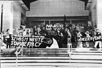 """Photo shows a large group of people in front of a building. Signs read slogans such as """"Smash white supremacy."""""""