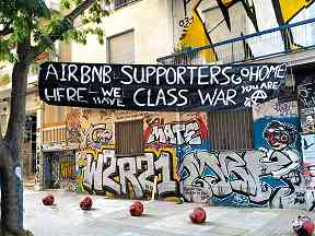 "Photo shows Greek and English grafitti. A banner reads, ""AirBnB Go Home, we have Class War."