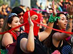 Photo shows women in a demonstration, centering on one with a red mask.