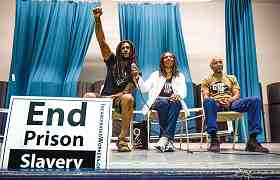 photo shows 3 people seated on a stage, a sign reading End Prison Slavery is in the foreground.