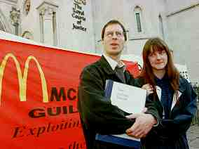 """Photo shows two young people standing in front of a banner reading """"McDonalds Guilty."""""""