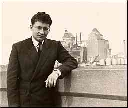 photo shows Guy Debord in his thirties in a contemplative pose in a nondescript urban setting