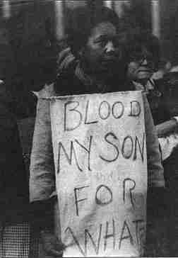 "Photo shows a young African-American man with a sign reading ""Blood of my son for what?"""