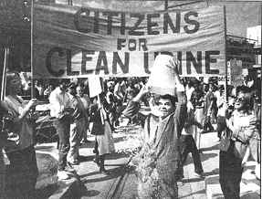 "photo shows a group of protesters with a large banner reading ""Citizens for Clean Urine."" An individual impersonating Ronald Reagan smiles as he empties a large bucket over his head."