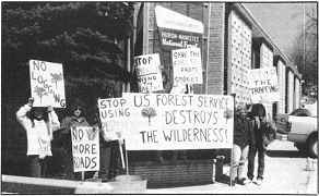 """Photo shows a small group of protesters. Signs read, """"Forest Service destroys wilderness"""" and """"Stop Logging."""""""