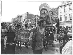 a black and white photo shows people marching in a street with flags, banners and a large puppet head
