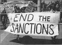 """photo shows a group of women protesters with signs and a banner that reads, """"End the Sanctions."""""""